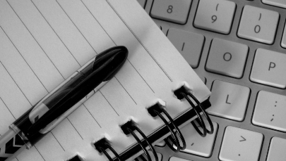 Image of a pen, notepad and keyboard, from the article Write For The Cause